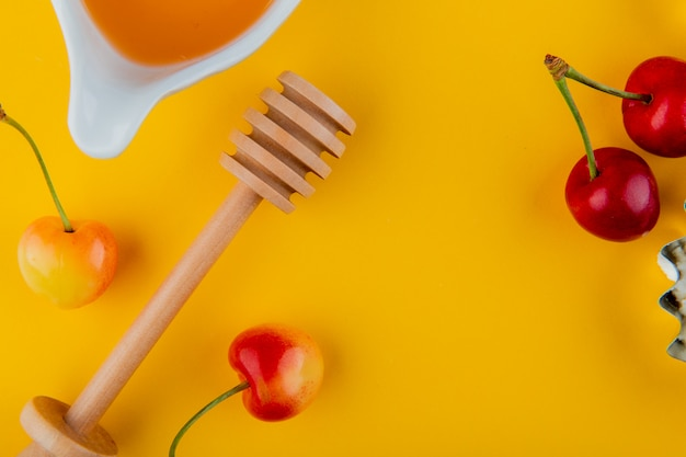 Draufsicht von honig mit holzlöffel und frischen reifen regnerischen kirschen auf gelb