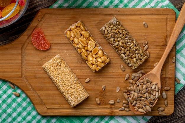 Draufsicht von honigriegeln mit erdnusssesam und sonnenblumenkernen auf einem holzbrett auf rustikalem
