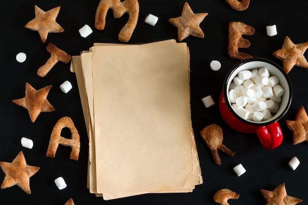 Draufsicht von ingwerplätzchen formte wie sterne und buchstaben und blätter des leeren papiers