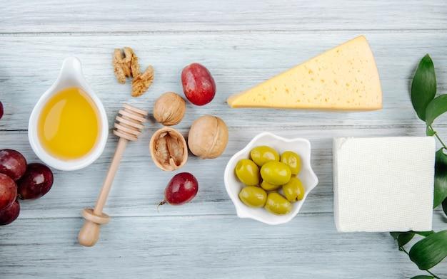 Draufsicht von käsestücken mit honig, frischer traube, eingelegten oliven und walnüssen auf grauem holztisch