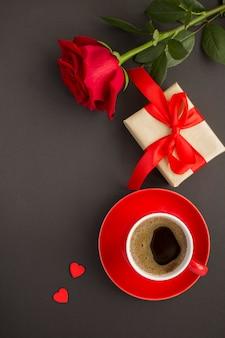 Draufsicht von kaffee, rose und geschenkbox auf dem schwarzen hintergrund