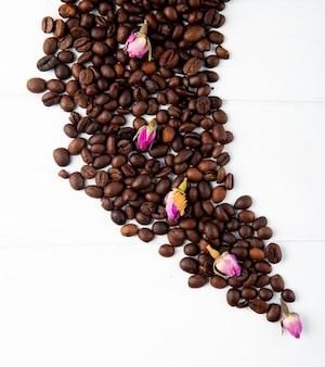 Draufsicht von kaffeebohnen und teerosenknospen verstreut auf weißem hintergrund