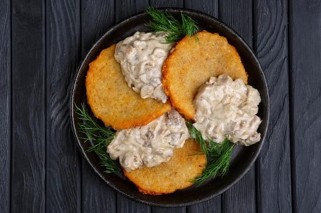 Draufsicht von kartoffel flapjacks (draniki) mit zwiebel und champignonsahnesauce in der gusseisenwanne