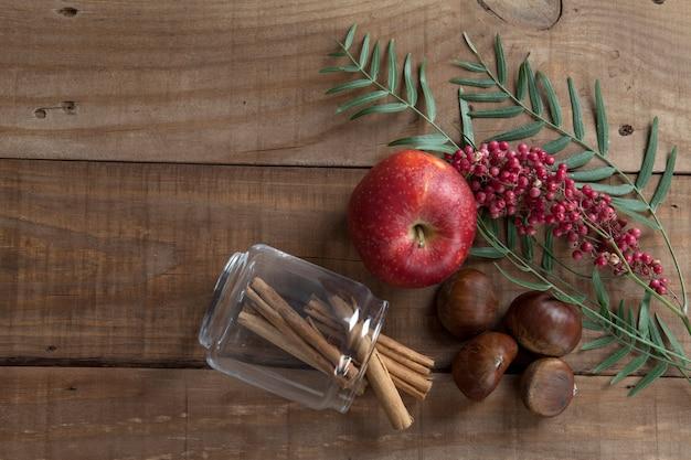 Draufsicht von kastanien und zimt, äpfeln, rosa pfeffer, auf einem hölzernen