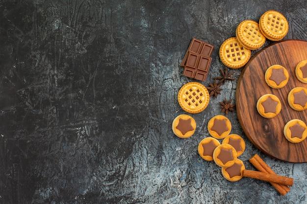 Draufsicht von keksen auf hölzernem teller mit anis und schokolade und zimt auf grauem hintergrund