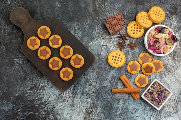 Draufsicht von keksen auf hölzernem teller und trockenen blumen auf grauem hintergrund