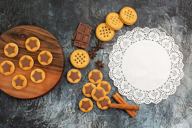 Draufsicht von keksen auf hölzernem teller und weißer spitze mit zimt und schokolade auf grauem hintergrund