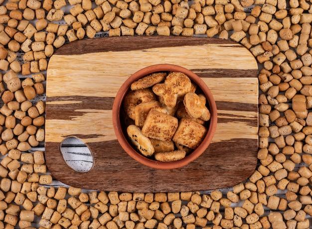 Draufsicht von keksen auf schneidebrett und auf crackerstruktur horizontal