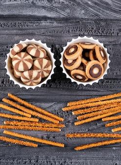 Draufsicht von keksen in schalen und crackern auf dunkler vertikale