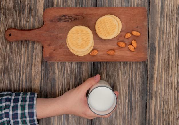 Draufsicht von keksen und mandeln auf schneidebrett und männlicher hand, die glas milch auf holztisch halten