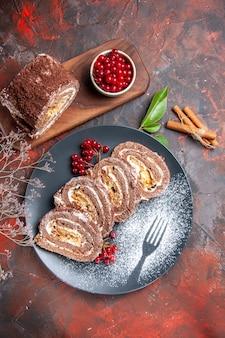 Draufsicht von keksrollenscheiben mit früchten auf dunkler oberfläche