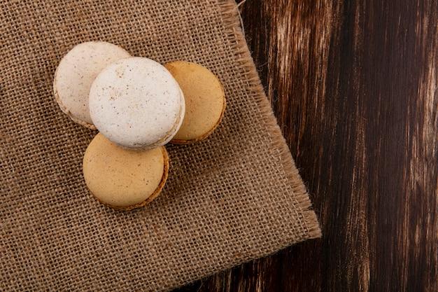 Draufsicht von kekssandwiches auf sackleinen und hölzernem hintergrund mit kopienraum