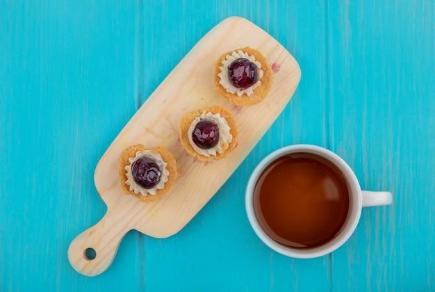 Draufsicht von kirschcupcakes auf schneidebrett und tasse tee auf blauem hintergrund