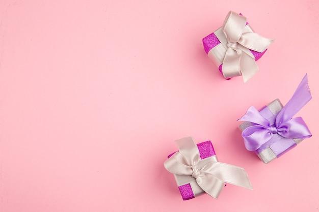 Draufsicht von kleinen geschenken auf rosa oberfläche