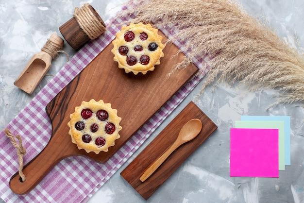 Draufsicht von kleinen kuchen, die köstlich und mit früchten auf leichtem, gebackenem süßem kuchen gebacken werden, backen kuchenfrucht