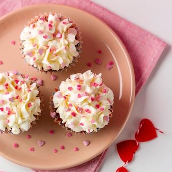 Draufsicht von kleinen kuchen mit herz-förmigem besprüht und dem bereifen