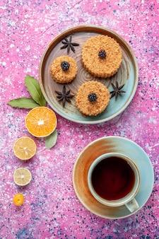 Draufsicht von kleinen leckeren kuchen süß und köstlich innenplatte mit tee auf der rosa oberfläche