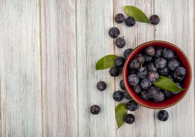 Draufsicht von kleinen sauren dunkelvioletten fruchtschollen auf einer schüssel mit blättern auf einem grauen hölzernen hintergrund mit kopienraum