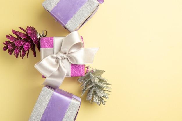 Draufsicht von kleinen weihnachtsgeschenken auf hellgelber oberfläche