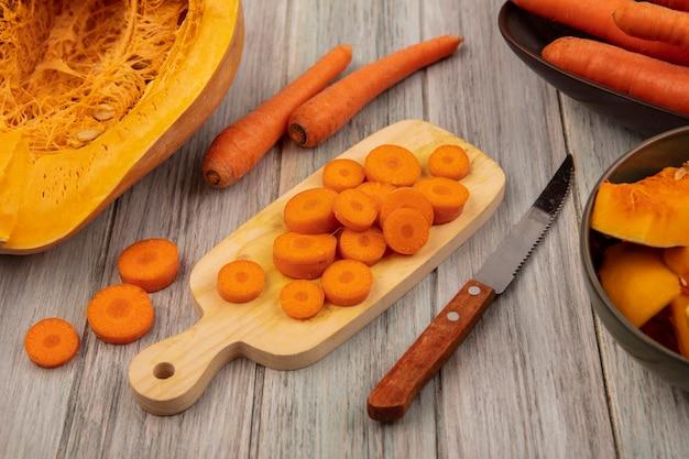 Draufsicht von knusprigen gehackten karotten auf einem hölzernen küchenbrett mit messer mit karotten auf einer schüssel mit kürbis lokalisiert auf einem grauen hölzernen hintergrund