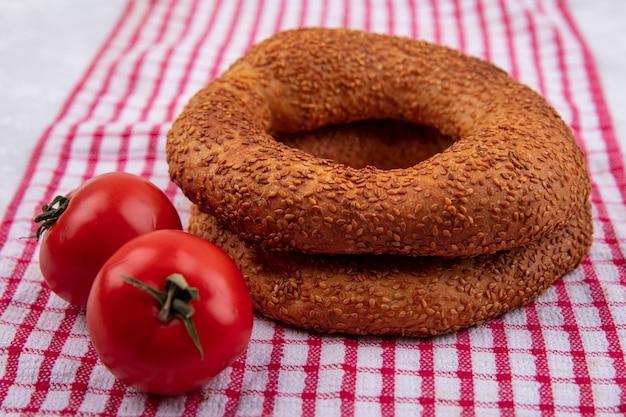 Draufsicht von knusprigen weichen traditionellen türkischen bagels mit frischen tomaten auf einem roten karierten tuch auf einem weißen hintergrund