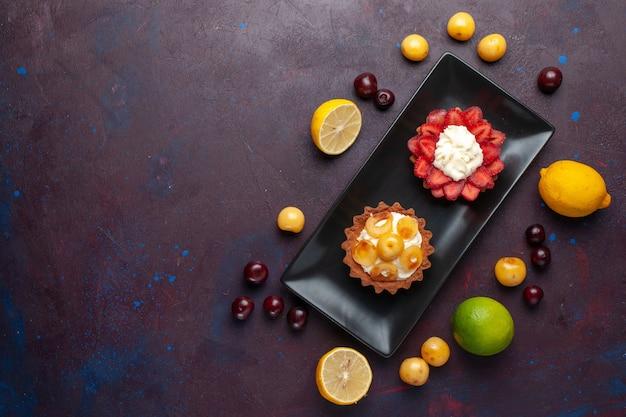 Draufsicht von köstlichen cremigen kuchen innerhalb platte mit frischen zitronen und früchten auf dunklem boden obstkuchen keks süß backen