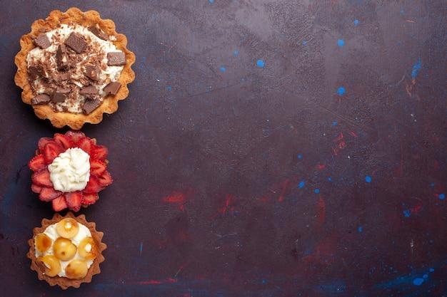 Draufsicht von köstlichen kuchen mit sahne-schokolade auf dunklem boden obstkuchen kekszucker süß