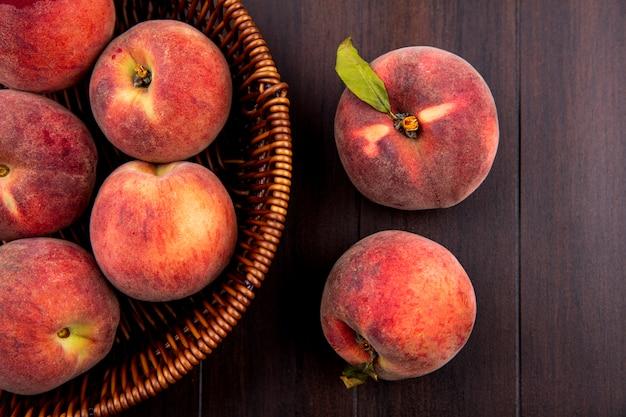 Draufsicht von köstlichen und saftigen pfirsichen auf eimer auf holz