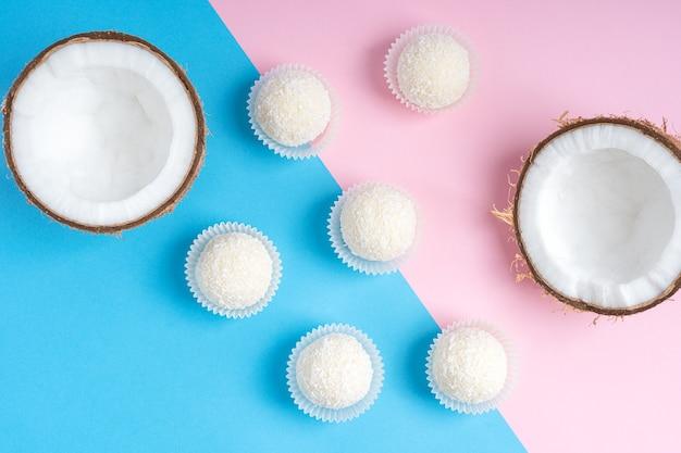 Draufsicht von kokosnuss-trüffeln oder energiekugeln, die auf trendigem buntem rosa und blauem hintergrund liegen