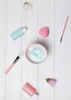 Draufsicht von kosmetischen einzelteilen auf hölzernem hintergrund