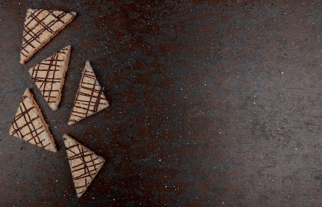 Draufsicht von kuchen auf schwarzem und kastanienbraunem hintergrund mit kopienraum