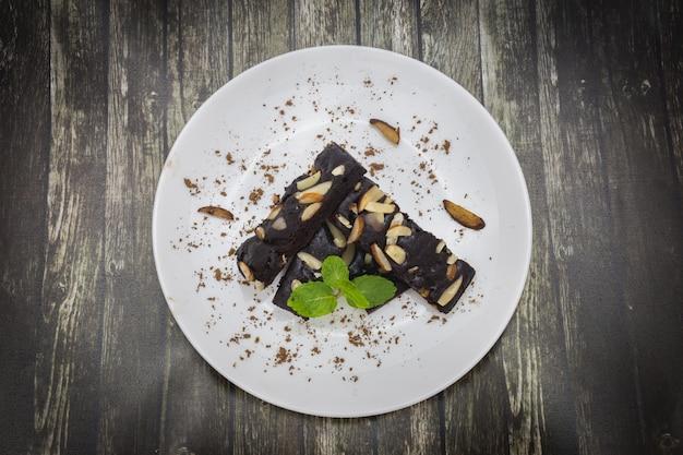 Draufsicht von kuchenschokoladenkuchen mit nüssen und minze auf weißer platte und hölzernem backgroun