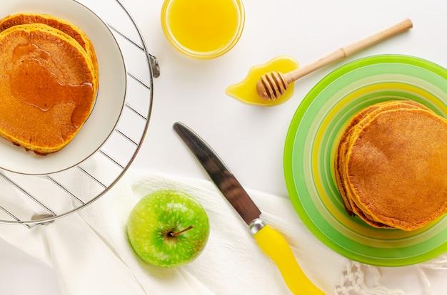 Draufsicht von kürbispfannkuchen und -honig auf weiß
