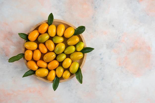 Draufsicht von kumquats und blättern auf hölzernem teller