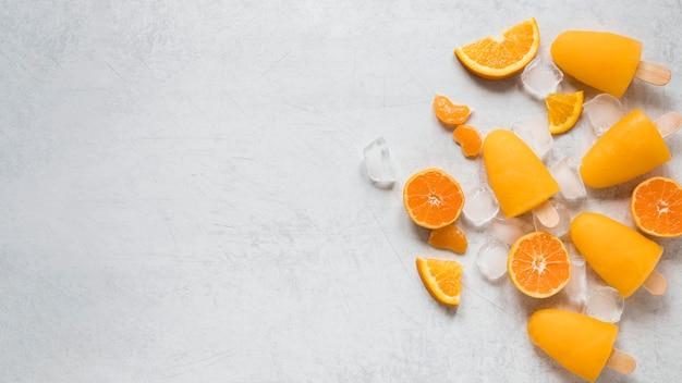 Draufsicht von leckeren eis am stiel mit orange und kopierraum