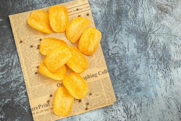 Draufsicht von leckeren hausgemachten pommes auf zeitung auf grauem tisch