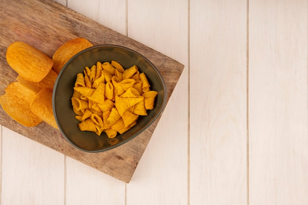 Draufsicht von leckeren knusprigen kegelform-maissnacks auf einer schüssel auf einem hölzernen küchenbrett auf einem beigen holztisch mit kopierraum