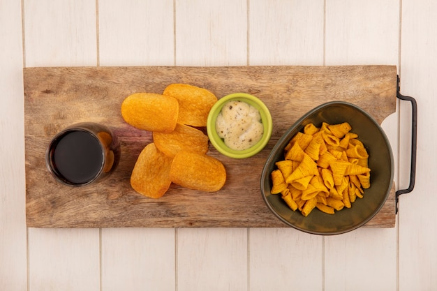 Draufsicht von leckeren knusprigen kornförmigen maissnacks auf einer schüssel auf einem hölzernen küchenbrett mit einem glas cola mit soße auf einem beigen holztisch