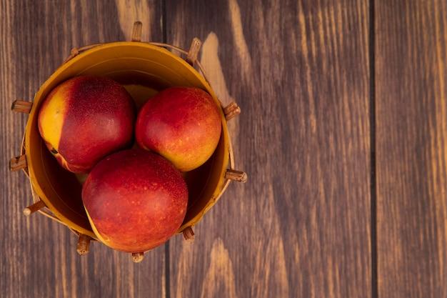 Draufsicht von leckeren saftigen pfirsichen auf einem eimer auf einer holzwand mit kopierraum