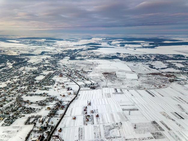 Draufsicht von leeren schneebedeckten feldern am wintermorgen auf drastischem hintergrund des bewölkten himmels. luftdrohnen-fotografiekonzept.