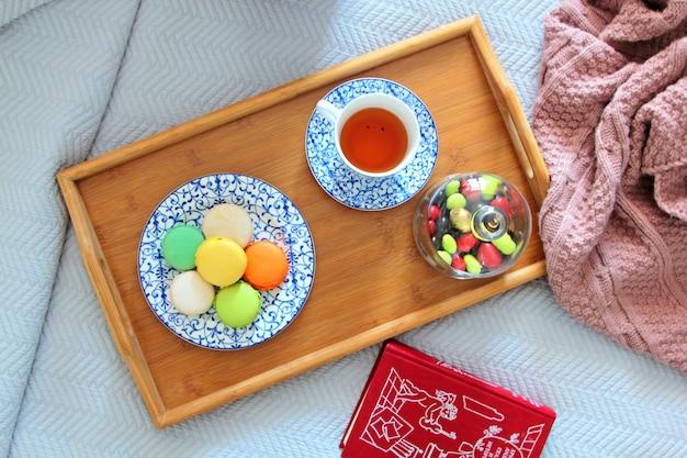 Draufsicht von makronen auf einem teller serviert mit tee auf einem holztablett