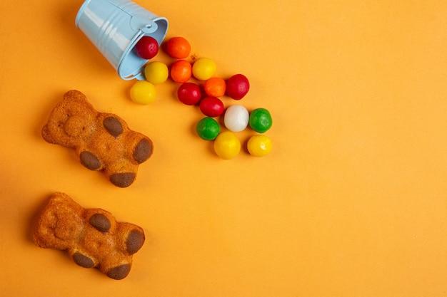 Draufsicht von mehrfarbigen pralinen, die von kleinen eimer- und biskuitkuchen in einer form des bären auf gelb verstreut sind