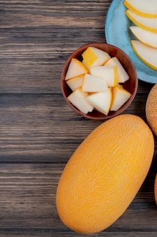 Draufsicht von melonenscheiben in der schüssel mit ganzen und geschnittenen auf hölzernem hintergrund