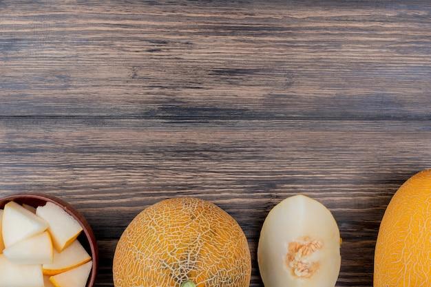 Draufsicht von melonenscheiben in der schüssel mit geschnittenen und ganzen auf hölzernem hintergrund mit kopienraum