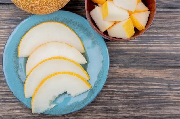 Draufsicht von melonenscheiben in platte mit ganzen und geschnittenen auf hölzernem hintergrund