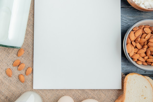 Draufsicht von milchprodukten als milchhüttenkäse-mandeln um notizblock auf sackleinen und hölzernem hintergrund mit kopienraum