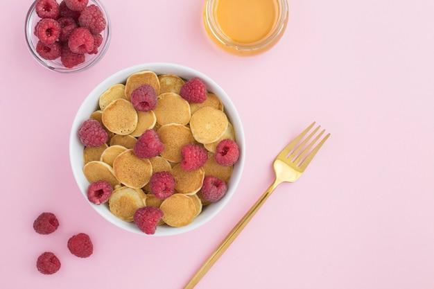 Draufsicht von mini-pfannkuchen mit himbeeren in der weißen schüssel auf der rosa oberfläche