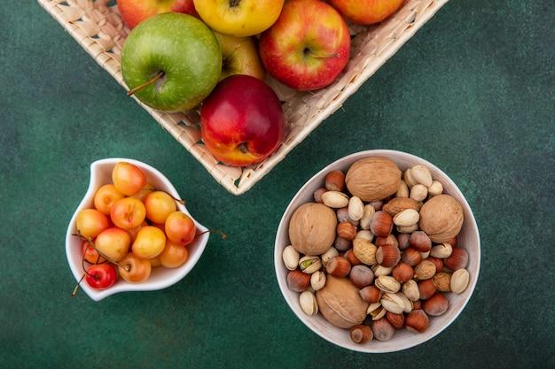 Draufsicht von mischnüssen mit weißen kirschen und äpfeln in einem korb auf einer grünen oberfläche