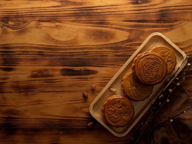 Draufsicht von mondkuchen auf holztablett und kopienraum auf rustikalem tisch. das chinesische schriftzeichen auf dem mondkuchen steht auf englisch für