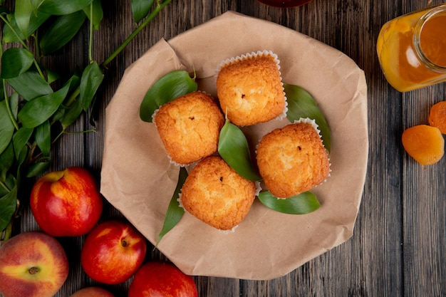 Draufsicht von muffins mit grünen blättern auf handwerklichem braunem papier mit frischen reifen nektarinen auf rustikalem holztisch